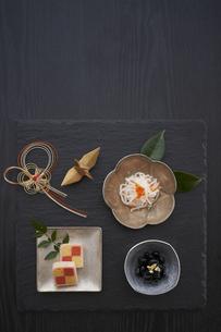 黒の石板に乗った小鉢の料理と水引の正月飾りと金色の鶴の写真素材 [FYI04833786]