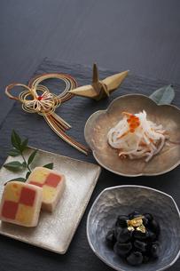 黒の石板に乗った小鉢の料理と水引の正月飾りと金色の鶴の写真素材 [FYI04833787]
