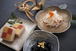 黒の石板に乗った小鉢の料理と水引の正月飾りと金色の鶴の写真素材 [FYI04833789]