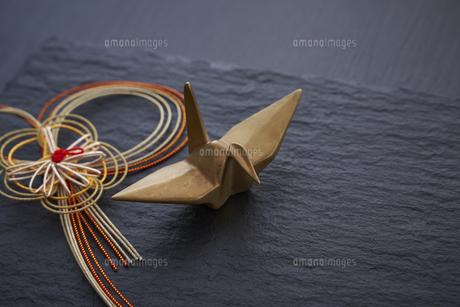 黒い石板の上の水引の正月飾りと金色の鶴の写真素材 [FYI04833790]