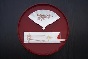 黒い天板の上の丸いお盆と祝箸とお皿の写真素材 [FYI04833796]