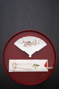 黒い天板の上の丸いお盆と祝箸とお皿の写真素材 [FYI04833797]