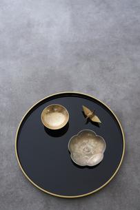 黒の丸盆の上の金杯と梅の形の小皿と金の鶴の写真素材 [FYI04833803]