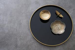 黒の丸盆の上の金杯と梅の形の小皿と金の鶴の写真素材 [FYI04833805]