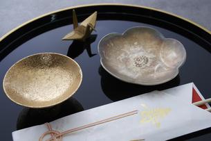 黒の丸盆の上の金杯と梅の形の小皿と金の鶴に祝い箸の写真素材 [FYI04833806]