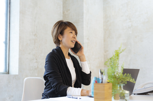 スマートフォンで話す日本人ビジネスウーマンの写真素材 [FYI04834867]