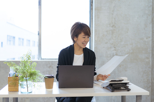 デスクワークをする日本人ビジネスウーマンの写真素材 [FYI04834869]