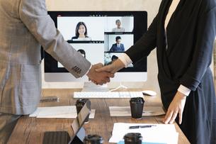 オンラインミーティングのモニターの前で握手をするビジネスマンの写真素材 [FYI04834890]