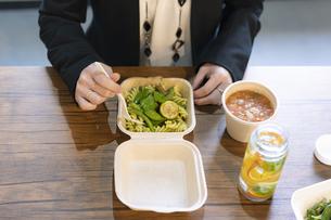 テイクアウトフードで食事をする女性の手元の写真素材 [FYI04834903]