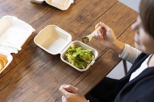 テイクアウトフードで食事をする女性の写真素材 [FYI04834904]