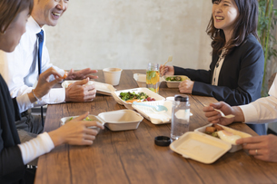 テイクアウトフードで食事をするビジネスマンとビジネスウーマンの写真素材 [FYI04834906]