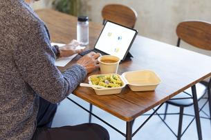タブレットPCを見ながらテイクアウトフードで食事をする男性の手元の写真素材 [FYI04834907]