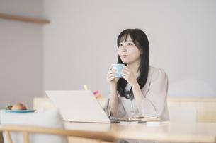 在宅での仕事中に休憩する女性の写真素材 [FYI04835423]