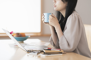 在宅での仕事中に休憩する女性の写真素材 [FYI04835427]