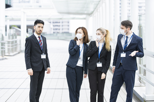 マスクがなくて周囲に避けられるビジネスマンの写真素材 [FYI04835473]