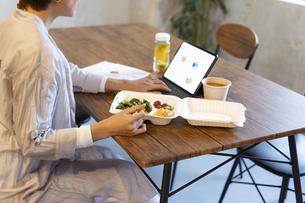 タブレットPCを見ながらテイクアウトフードで食事をするミドル女性の写真素材 [FYI04835517]