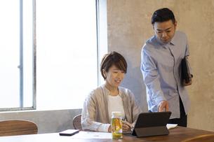 タブレットPCを見る日本人ビジネスウーマンとビジネスマンの写真素材 [FYI04835521]