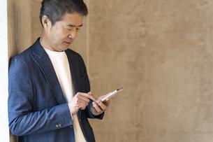 スマートフォンを見るシニア世代の日本人ビジネスマンの写真素材 [FYI04835546]