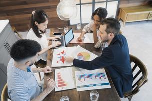カジュアルな雰囲気のオフィス空間でミーティングするビジネスマンたちの写真素材 [FYI04835979]