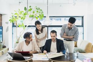 カジュアルな雰囲気のオフィス空間でミーティングするビジネスマンたちの写真素材 [FYI04835984]