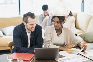 カジュアルな雰囲気のオフィス空間でミーティングするビジネスマンたちの写真素材 [FYI04835990]