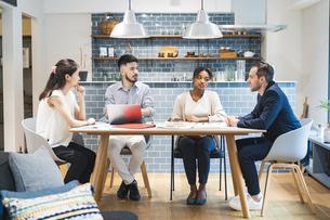 カジュアルな雰囲気のオフィス空間でミーティングするビジネスマンたちの写真素材 [FYI04835997]