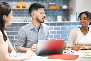 カジュアルな雰囲気のオフィス空間でミーティングするビジネスマンたちの写真素材 [FYI04836008]