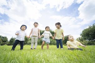 青空の下、元気に走る子供たちの写真素材 [FYI04836071]