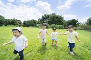 青空の下、元気に走る子供たちの写真素材 [FYI04836074]
