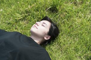 草原でリラックスする女性の写真素材 [FYI04836169]