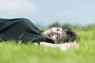 草原でリラックスする女性の写真素材 [FYI04836171]
