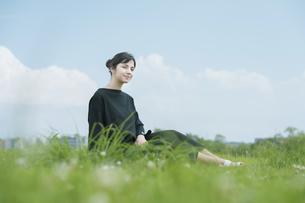 草原でリラックスする女性の写真素材 [FYI04836217]