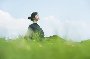 草原でリラックスする女性の写真素材 [FYI04836218]