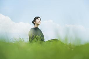 草原でリラックスする女性の写真素材 [FYI04836219]