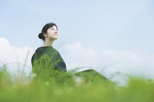 草原でリラックスする女性の写真素材 [FYI04836221]