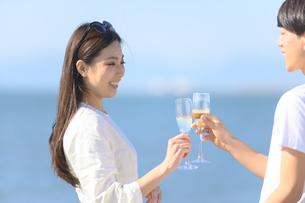 海岸でシャンパンを飲むカップルの写真素材 [FYI04836450]