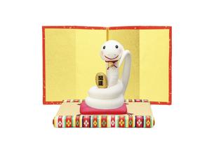 金屏風の前で招き猫の真似をする白いヘビの写真素材 [FYI04837021]