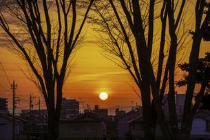 丘の上から、町並みの向こうに昇る春の日の出 景色の良い尾張一宮パーキングエリアの写真素材 [FYI04837849]