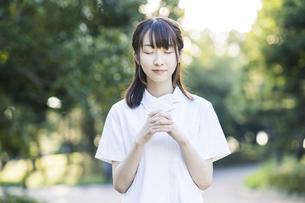 お祈りのポーズをする白衣の女性の写真素材 [FYI04838342]