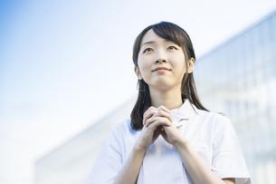 お祈りのポーズをする白衣の女性の写真素材 [FYI04838346]