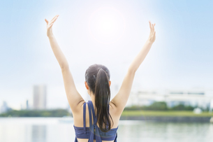 都市のビーチでストレッチと深呼吸をする若い女性の写真素材 [FYI04838347]