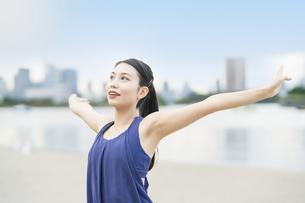 都市のビーチでストレッチと深呼吸をする若い女性の写真素材 [FYI04838350]