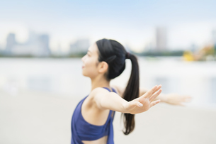 都市のビーチでストレッチと深呼吸をする若い女性の写真素材 [FYI04838353]