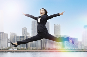 笑顔でジャンプする若いビジネスウーマン・就職活動生の写真素材 [FYI04838355]
