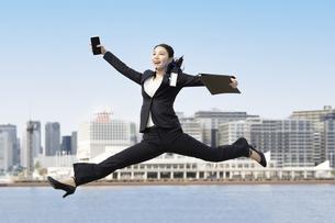 笑顔でジャンプする若いビジネスウーマン・就職活動生の写真素材 [FYI04838360]