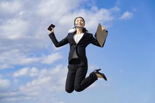 笑顔でジャンプする若いビジネスウーマン・就職活動生の写真素材 [FYI04838361]