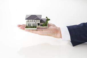 家の模型を持ったセールスマンの写真素材 [FYI04838645]