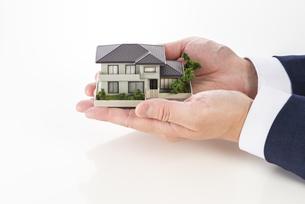 家の模型を持ったセールスマンの写真素材 [FYI04838648]