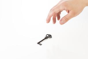 鍵を持つ男性の手の写真素材 [FYI04838655]