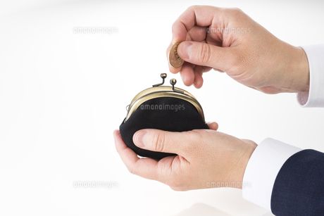 がま口財布を持ったビジネスマンの手の写真素材 [FYI04838671]